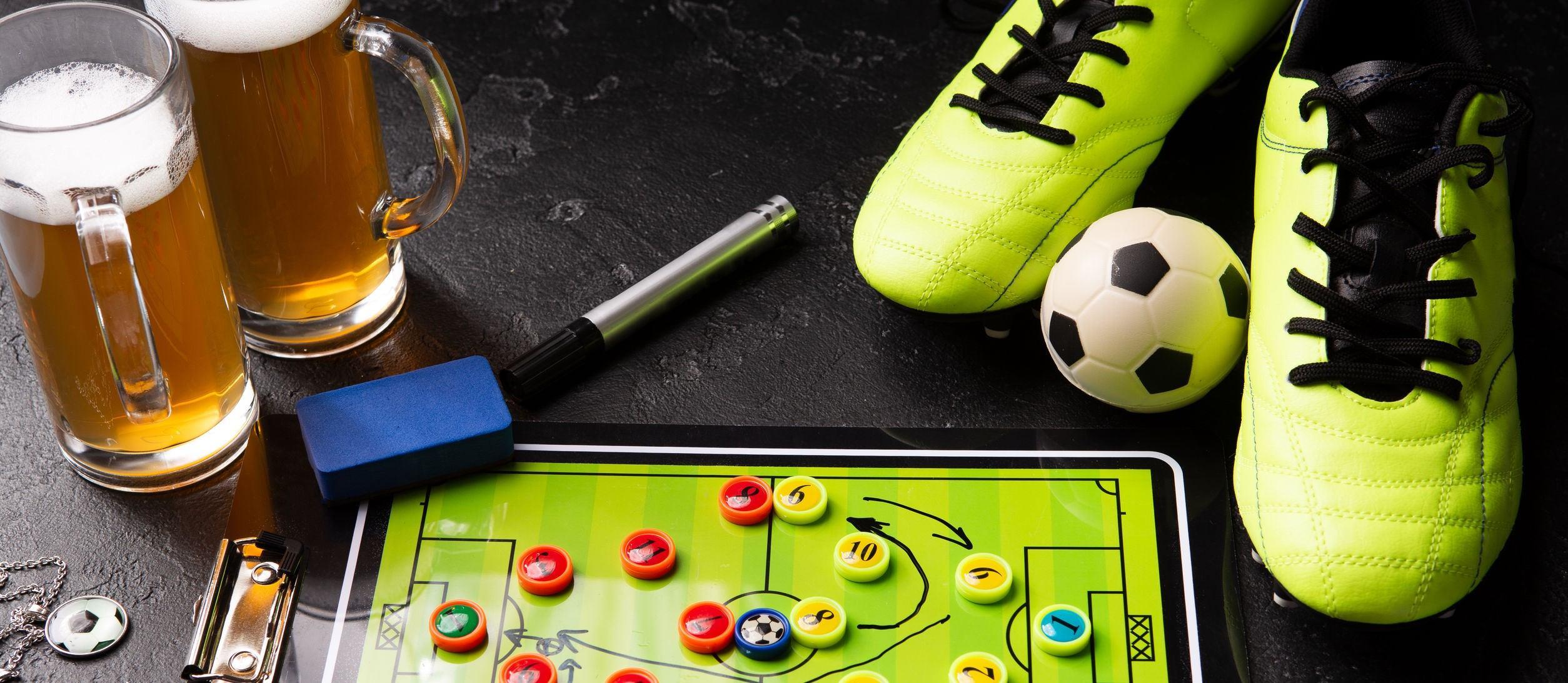 Photo de deux chopes de bière en mousse, d'un baby-foot, d'un ballon, de chaussures de football, d'un tuyau et d'un hochet sur une table noire.